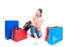 Frau, die Geschenk oder Einkaufstasche untersucht und überrascht glaubt Stockbilder