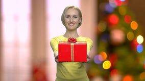 Frau, die Geschenkbox auf abstraktem Weihnachtshintergrund gibt stock footage