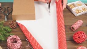 Frau, die Geschenkbox mit Ausrüstung einwickelt und Einzelteile auf der hölzernen Tabelle, bereitend für das Feiern von Weihnacht stock footage