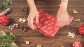 Frau, die Geschenkbox mit Ausrüstung einwickelt und Einzelteile auf der hölzernen Tabelle, bereitend für das Feiern von Weihnacht stock video footage