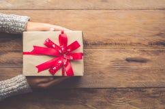 Frau, die Geschenke für spezielle Momente mit Special der auf Holz hält Lizenzfreie Stockfotografie