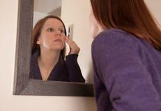 Frau, die Gesicht im Spiegel betrachtet Lizenzfreie Stockfotografie