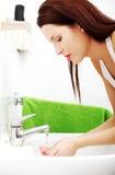 Frau, die Gesicht mit Wasser spritzt Stockfotografie
