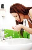 Frau, die Gesicht mit Wasser spritzt Lizenzfreies Stockbild