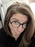 Frau, die Gesichter in den Gläsern macht Lizenzfreie Stockfotos