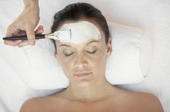 Frau, die Gesichtsbehandlung im Badekurort bekommt Stockbilder