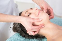 Frau, die Gesichtskopfmassage im Badekurortsalon genießt Lizenzfreie Stockfotos