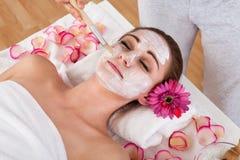 Frau, die Gesichtsmaske am Badekurortstudio erhält Stockfotos