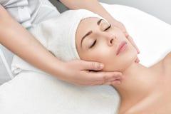 Frau, die Gesichtsmassage am Badekurortsalon empfängt stockfoto