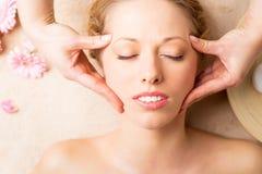 Frau, die Gesichtsmassage am Badekurortstudio empfängt Lizenzfreies Stockfoto