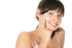 Frau, die Gesichtssahne aufträgt lizenzfreie stockbilder
