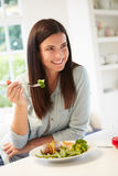 Frau, die gesunde Mahlzeit in der Küche isst stockbild