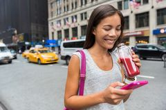 Frau, die gesunden Saft unter Verwendung Telefon App trinkt stockfotografie