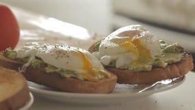 Frau, die gesundes Frühstück mit Avocado auf gebratenem Brot, Eiern und Tomate zubereitet stock footage