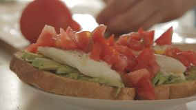 Frau, die gesundes Frühstück mit Avocado auf gebratenem Brot, Eiern und Tomate zubereitet stock video footage