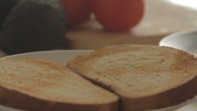 Frau, die gesundes Frühstück mit Avocado auf gebratenem Brot, Eiern und Tomate zubereitet stock video