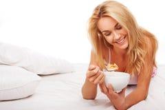 Frau, die Getreide im Bett isst Stockfotografie