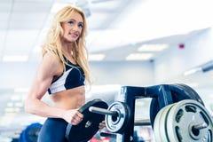Frau, die Gewichte vom Stand in der Eignungsturnhalle nimmt Lizenzfreie Stockbilder
