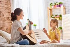 Frau, die Gitarre für Kindermädchen spielt lizenzfreie stockfotos