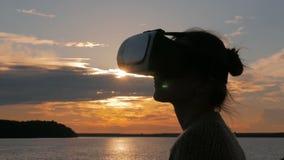 Frau, die Gläser der virtuellen Realität auf Plattform des Kreuzschiffs bei Sonnenuntergang verwendet stock footage