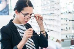 Frau, die Gläser am Optiker vergleicht Lizenzfreie Stockbilder