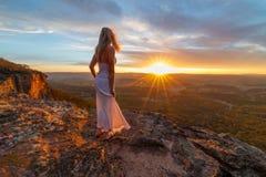 Frau, die glückselige Sonnenuntergänge von versteckten Klippenleisten aufpasst stockfoto