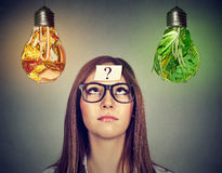 Frau, die Glühlampe der ungesunden Fertigkost und des grünen Gemüses betrachtet Lizenzfreies Stockbild