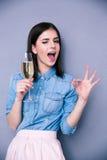 Frau, die Glas Champagner hält und okaygeste zeigt Stockfotografie
