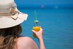 Frau, die Glasflasche frischen Orangensaft hält und betrachtet Stockfotografie