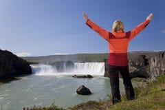 Frau, die am Godafoss Wasserfall, Island feiert Lizenzfreies Stockfoto