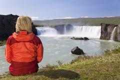 Frau, die am Godafoss Wasserfall in Island sitzt Stockfotos