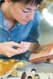 Frau, die an Goldrahmen arbeitet lizenzfreies stockfoto