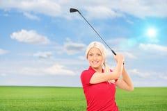 Frau, die Golf auf einem Gebiet spielt Lizenzfreies Stockbild