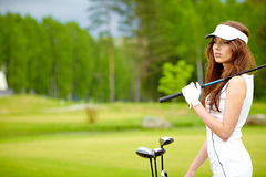 Frau, die Golf auf einer grünen Frau spielt stockfotografie