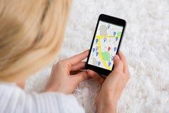Frau, die GPS-Karte auf Mobiltelefon verwendet Lizenzfreie Stockbilder