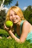 Frau, die grünen Apfel auf der Sommerlichtung isst lizenzfreie stockfotos