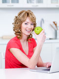 Frau, die grünen Apfel in der Küche isst Stockbild