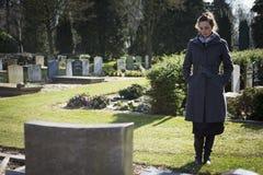 Frau, die am Grabstein steht lizenzfreie stockbilder
