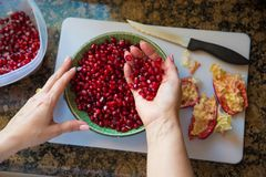 Frau, die Granatäpfel zubereitet Lizenzfreies Stockbild