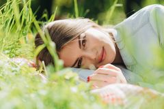 Frau, die in Gras legt Lizenzfreie Stockfotografie