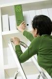Frau, die grünes Faltblatt vom Regal löscht Stockbild