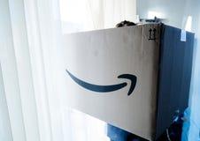 Frau, die große Amazon Prime-Paketpappe hält lizenzfreie stockfotos