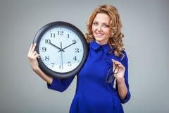 Frau, die große Uhr hält Stockfotografie