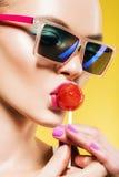 Frau, die großen roten Lutscher in der blauen Sonnenbrille isst Lizenzfreie Stockfotos