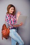 Frau, die Grußgeste zur Web-Kamera zeigt Stockfotos