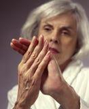 Frau, die Hände in den Schmerz betrachtet Stockbild