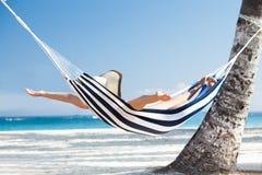 Frau, die in Hängematte am Strand ausdehnt Stockfoto
