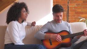 Frau, die hört, um Gitarre zu Hause spielen zu bemannen stock video