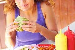 Frau, die Hühnerverpackungs-Sandwich isst lizenzfreie stockfotos