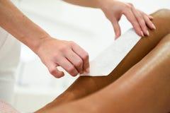 Frau, die Haarabbauverfahren auf dem Bein anwendet Wachsstreifen hat stockfotografie